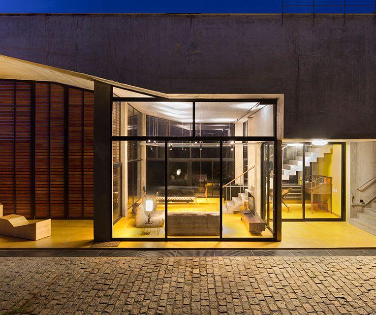 A sala de estar, com mobiliário de base neutra, é separada da sala de jantar e cozinha, por uma escada interna