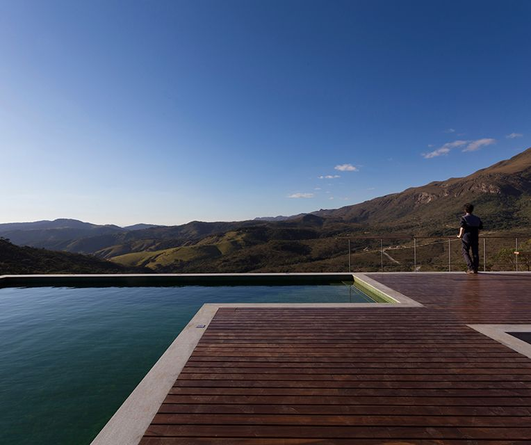 Os três quartos, de grandes janelões, são encaixados em uma caixa de concreto diretamente abaixo da piscina.
