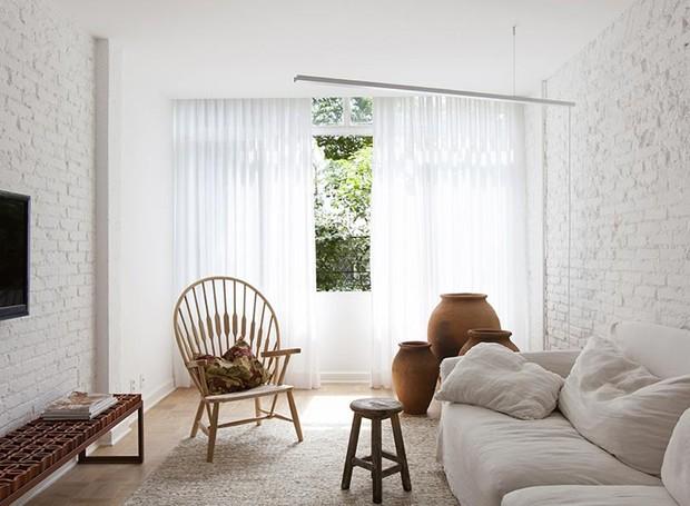 sala-sofa-tv-janela-branco-neutro-tijolos-aparentes-cortina-poltrona