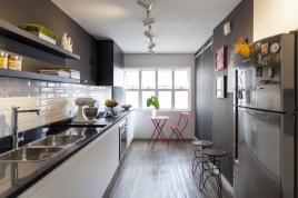 A cozinha tem paredes pintadas de preto e outra revestida com azulejos