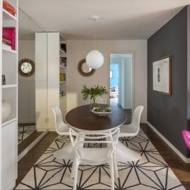 O cinza da parede oposta imprime maior destaque ao mobiliário