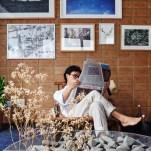 Rodrigo na poltrona da Decarvalho Atelier, sob fotografias de Eduardo Muylaert, Cássio Vasconcellos e outros