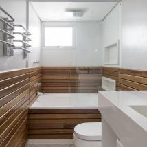 Na suíte principal, uma estrutura de madeira abraça a banheira para deixar o ambiente mais acolhedor Foto: Julia Ribeiro/Divulgação