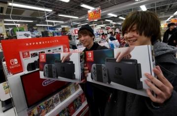Os amigos Hiroki Higuchi e Tomohiro Yagi, ambos de 20 anos, exibem seus novos Nintendo Switch, comprados em Tóquio