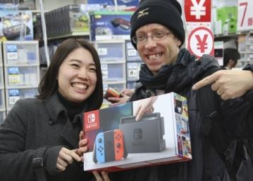 David Flores e sua esposa Nao Imoto exibem seu novo videogame, o Switch, na Bic Galaxy, loja de videogames em Tóquio