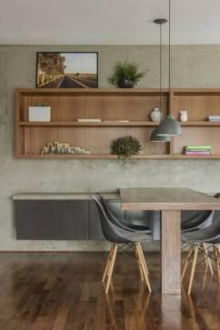 Uma bancada de concreto percorre todo o apartamento. Na sala de estar, a peça que é fixa na parede apoia a mesa para refeições Foto: Zeca Wittner/Estadão