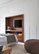 QUARTO DO CASAL   Em meio aos armários brancos, um nicho de nogueira-americana posiciona a TV diante da cama. Pufe da Codex Home e tapete da By Kamy (Foto Denilson Machado/MCA Estúdio/Divulgação)