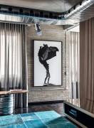 SALA DE TV   Sobre a parede de tijolinhos, a foto de Guilherme Licurgo destaca-se ao lado da mesa da Prototype. Junto ao painel ripado de nogueira-americana, onde fica a TV, há um móvel com espelho bronze desenhado pelos arquitetos (Foto Denilson Machado/MCA Estúdio/Divulgação)
