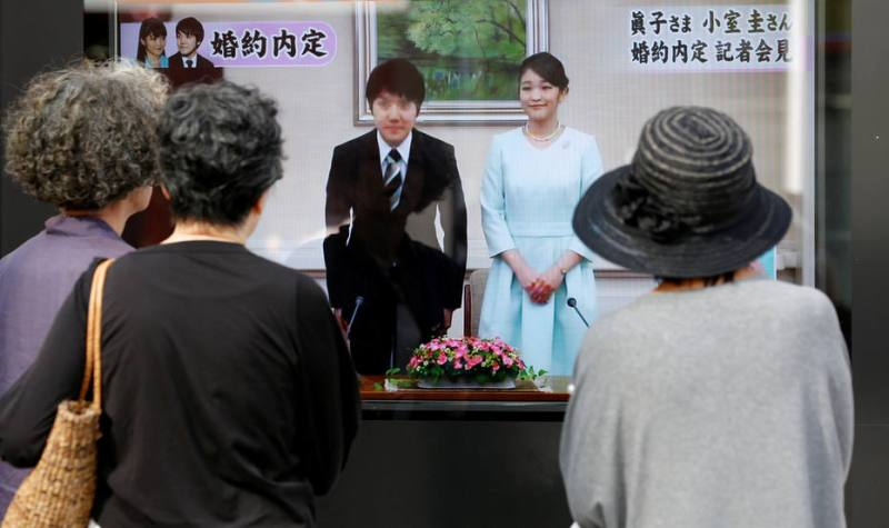 People look at a street monitor showing a news report about the engagement of Princess Mako, the elder daughter of Prince Akishino and Princess Kiko, and her fiancee Kei Komuro, a university friend of Princess Mako, in Tokyo