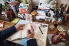 Sobre a escrivaninha há livros, mapas e cartões