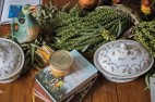 No detalhe da mesa de jantar, pato de louça francesa St. Clement e legumeira Vieux Paris (ambos do início do séc. 20), latas francesas de gésiers de pato, livros e plantas