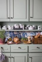 A prateleira e a bancada do armário da cozinha acomodam, entre outros itens, pratos de faiança franceses, canecas de taberna portuguesa (séc. 19), casinhas holandesas da KLMe, de fundo, jogos americanos da Olhar o Brasil