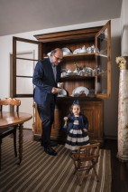 O morador e sua neta Rafaela junto ao guarda-louça português (séc. 19), que reúne a coleção de porcelanas Limoges e Vieux Paris, e à cadeira infantil francesa