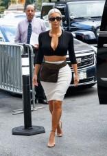 O cardigã novo de Azzedine Alaïa e a saia nova Calvin Klein se combinam com acessórios vintage: pochete Miu Miu e óculos de sol Versace