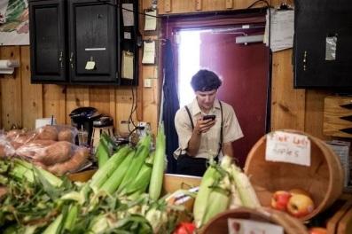 Atualmente, os celulares estão sendo usados por alguns membros da comunidade. Na banca de um produtor rural na Pensilvânia. (Ashley Gilbertson para The New York Times)