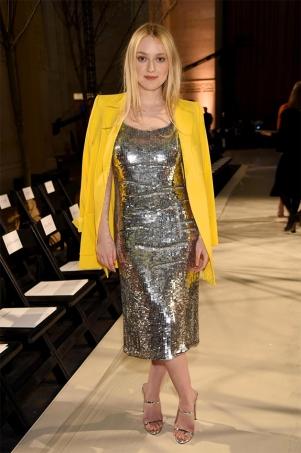 Dakota Fanning de vestido de paetê e casaco amarelo no desfile da Oscar de la Renta