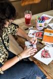 Ana trabalha em suas ilustrações sobre a mesa da Restoration Hardware