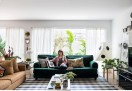 O living, onde Ana aparece sobre sofá da Ikea com almofadas de Jonathan Adler (à esq.) e da The Rug Company (à dir.), recebeu mesa lateral e banco de Alvar Aalto, da Artek, na Micasa, luminárias de mesa de Ana Neute (à esq.), na Amoreira, e de piso de Isamu Noguchi (à dir.), suportes de plantas da Selvvva, mesa de centro da Blu Dot e tapete da Phenicia Concept