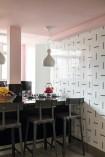 A cozinha revestida de azulejos da Lurca, com pendentes de Bianca Barbato e banquetas da Securit