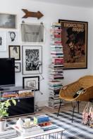 O canto do living recebeu aparador da USM, luminária de piso da Jieldé, estante, na Design Within Reach, cadeira de palha, na Loja Teo, e almofada de Alexander Girard para a Vitra, tudo sobre o tapete da Phenicia Concept
