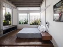 Dotado somente do essencial, com destaque para as luminárias de cabeceira da Reka, o quarto do morador é resguardado por janelas internas que integram o ambiente ao jardim