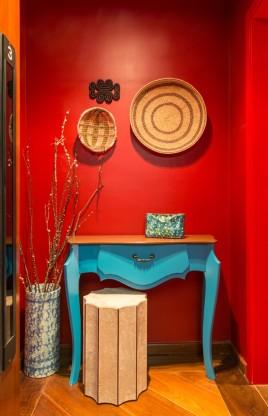 HALL DE ENTRADA | Com porta e paredes completamente vermelhas, o espaço é o cartão-postal do apartamento. As peças e obras de arte são do acervo dos moradores (Foto Evelyn Muller/Divulgação)
