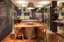 SALA DE JANTAR E INTEGRAÇÃO | A base da mesa de jantar, assim como o móvel multifuncional, foi projetada pelo escritório H2C Arquitetura e é de marcenaria com acabamento de concreto. Cadeiras de Fernando Jaeger. Pendentes da Reka. Ao fundo, na cozinha, piso de ladrilho hidráulico da Dalle Piagge. Armários no tom berinjela, da Kitchens (Foto Evelyn Muller/Divulgação)