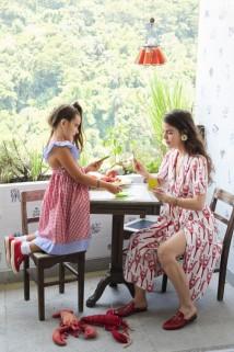 A stylist e a filha Antonia brincam na varanda com azulejos de Adriana Varejão guarnecendo a horta, móveis adquiridos na Feira do Rio Antigo e pendente de Ingo Maurer – Luciana veste Miu Miu e sapatos Gucci, e Antonia usa vestido criado pela mãe