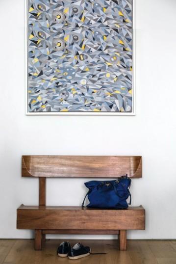 Logo na entrada da casa, o casal optou por expor um banco (1954) do luso-brasileiro Joaquim Tenreiro como peça única do ambiente, encabeçado por uma tela de Charles Meyers, pai de Zesty