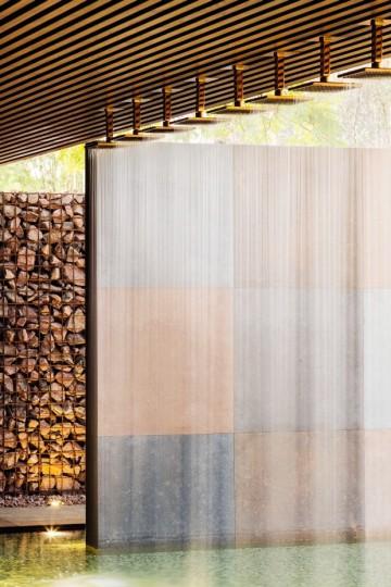 Outra vista do corredor de entrada destaca o efeito da iluminação projetada contra a água e as pedras