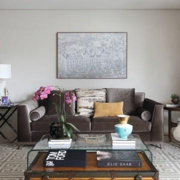 O living tem como ponto central uma mesa de vidro do acervo pessoal dos moradores, agora acompanhada do baú vintage ANA LUIZA WAWELBERG – na parede, gravura de Tarsila do Amaral