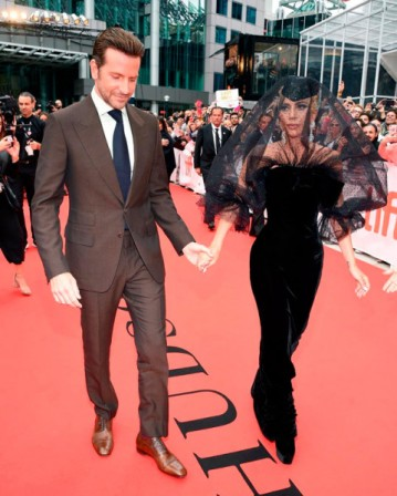 O look todo preto é de Giorgio Armani! Ela está acompanhada de Bradley Cooper, parceiro de elenco e diretor do filme