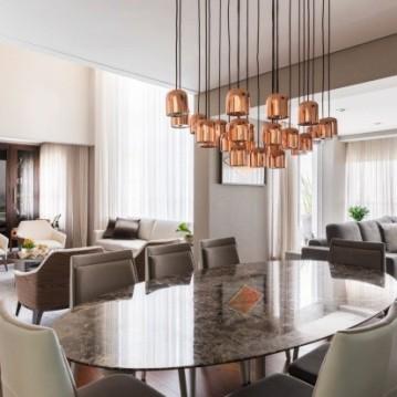 A sala de jantar recebeu mesa com tampo de mármore marrom imperial, cadeiras BRETON e pendente de cobre PONTOLUCE