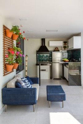 Para alcançar a atmosfera desejada, a arquiteta Érica Salguero investiu em um mix de frescor e leveza. Os vasos cor de barro em contraste com o painel de madeira escura criam um ambiente charmoso no quintal da casa Foto: Andre Nazareth